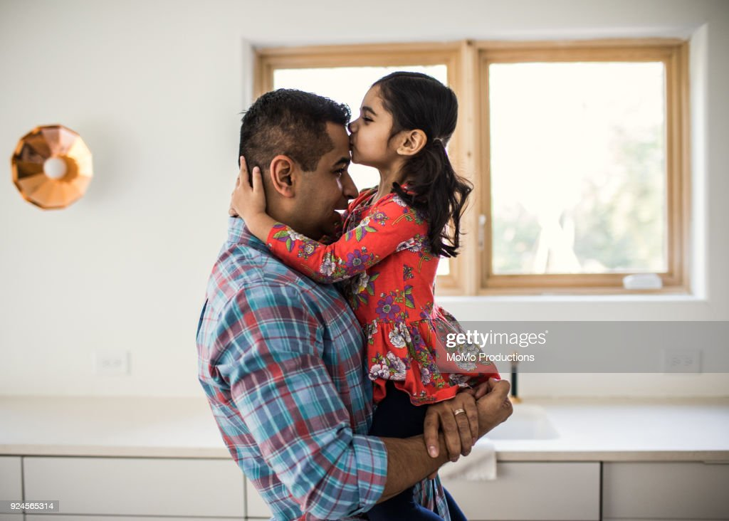 Daughter kissing father at home : Stock Photo
