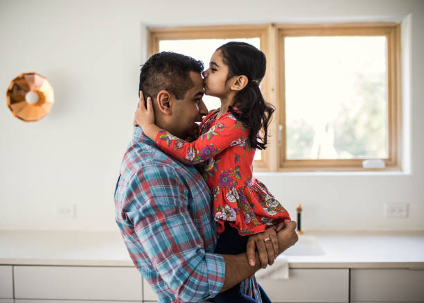 daughter kissing father at home - parents love kid stock pictures, royalty-free photos & images