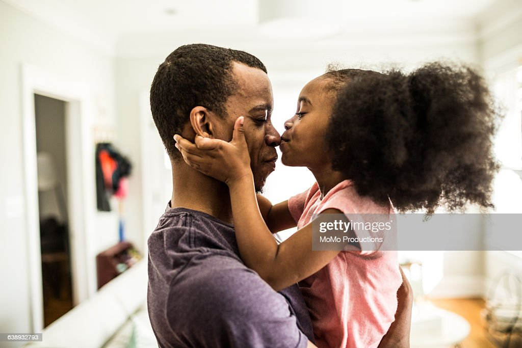 daughter kissing father on the nose : Stock Photo