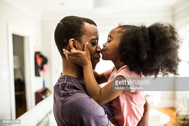 daughter kissing father on the nose - african american family home stock photos and pictures