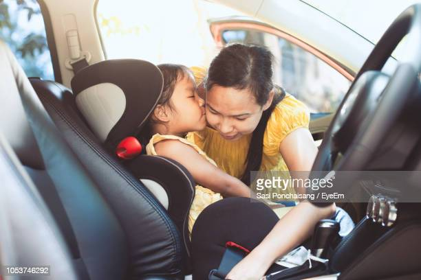 Daughter Kissing Mother Buckling Seat Belt While Sitting In Car
