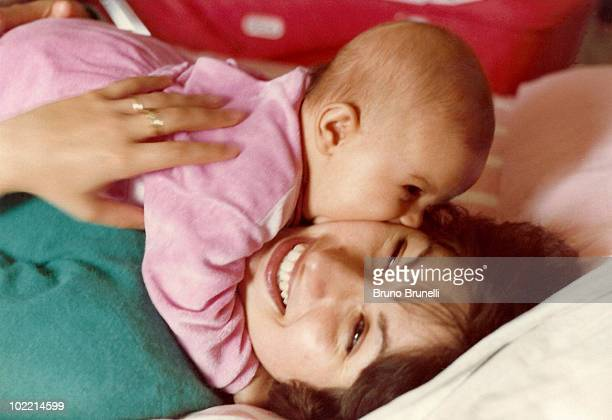 Daughter kissing mother in bed