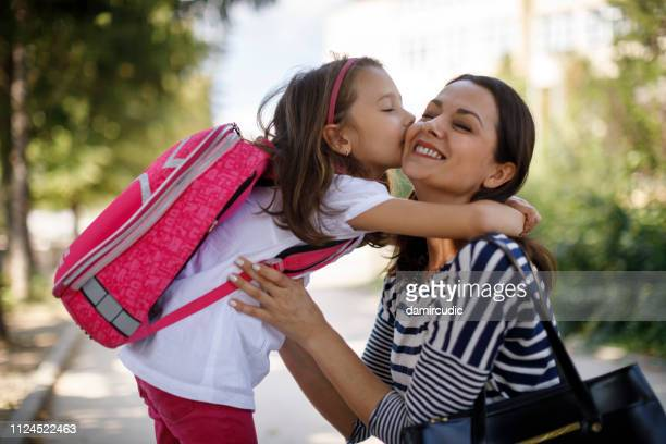daughter kissing mother in front of school - first day of school stock pictures, royalty-free photos & images