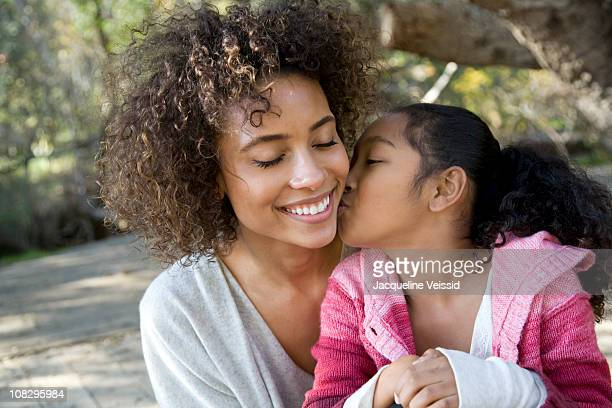 daughter kissing mother on cheek - indian girl kissing stock photos and pictures