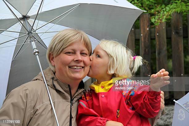 Daughter kissing mother under umbrella