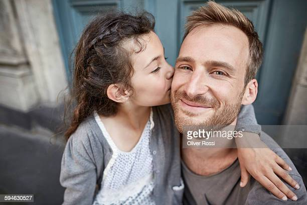 daughter kissing smiling father outdoors - father daughter stock pictures, royalty-free photos & images