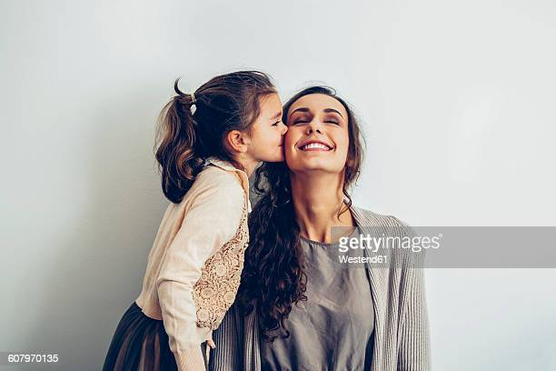 daughter kissing smiling mother's cheek - gratitude stock pictures, royalty-free photos & images