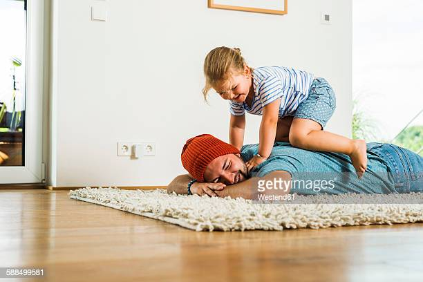 daughter kneeling on father's back lying on floor - human body part stock pictures, royalty-free photos & images