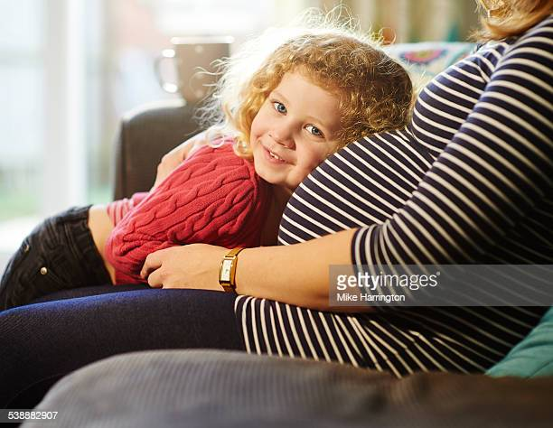 daughter laying on pregnant mothers bump - pregnancy stock pictures, royalty-free photos & images