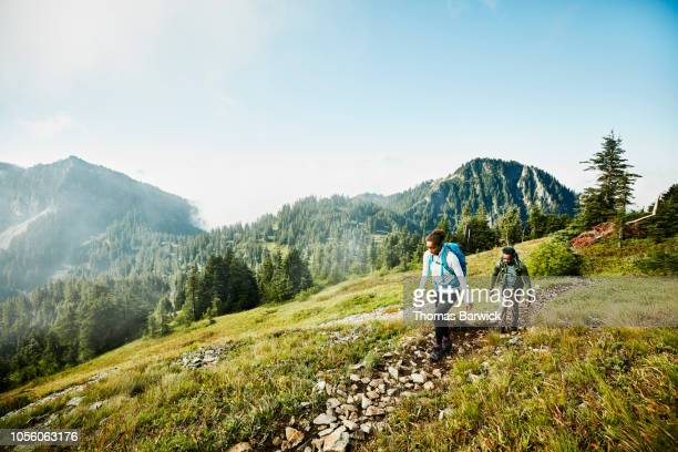 daughter leading father on morning hike up mountainside - avontuur stockfoto's en -beelden