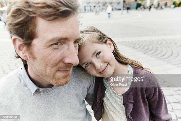 Daughter leaning against father's shoulder