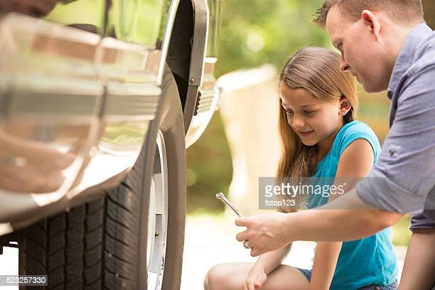 Daughter learning from father. Dad, child with tools, repairing vehicle.