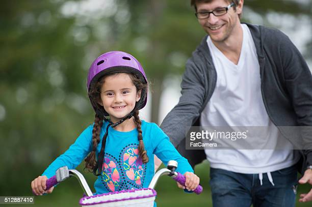 Daughter Learning How to Ride a Bike From Her Dad