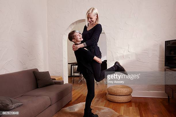 Daughter lifting mother up in the air.