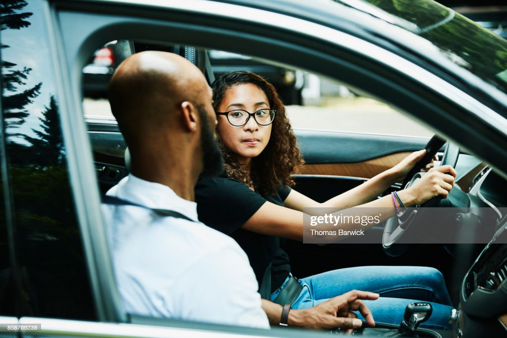 Daughter listening to fathers instructions while sitting in car before driving lesson : Stock Photo