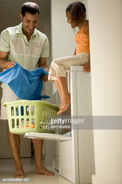 Daughter (6-7) looking at father doing laundry, smiling