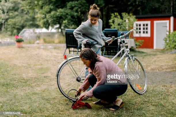 daughter looking at mother pumping bicycle in yard - inflating stock pictures, royalty-free photos & images