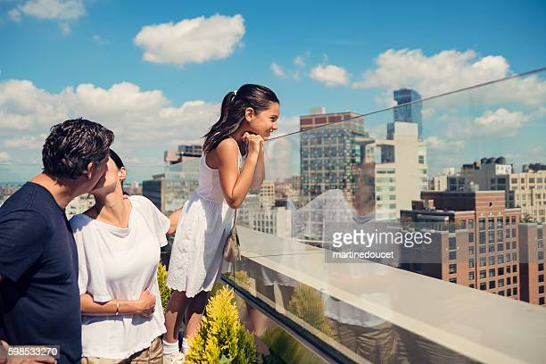 Daughter looking at New-York skyline while parents are kissing.