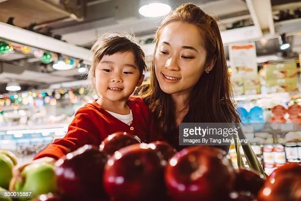 Daughter & mom choosing fruit in supermarket