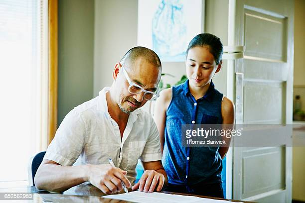 Daughter next to father as he fills out form