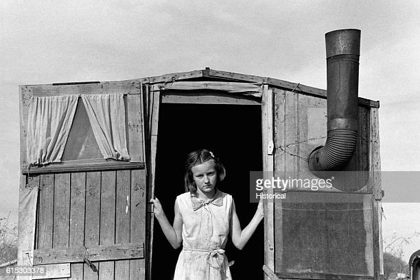 Daughter of a migrant agricultural worker standing in the doorway of a trailer in Sebastian Texas February 1939 | Location Sebastian Texas USA