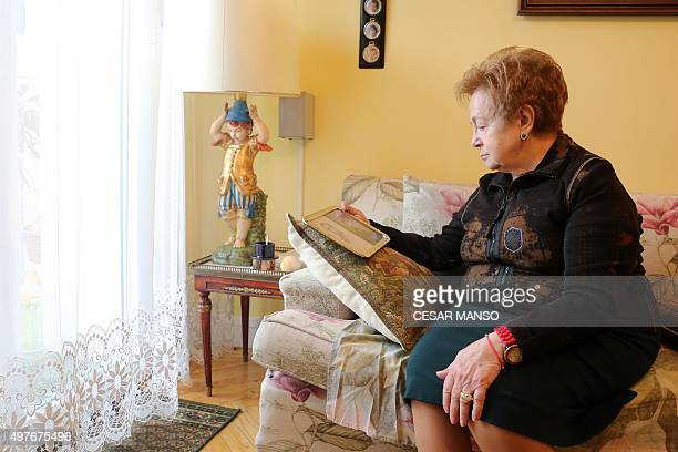 Daughter of Franco era victim Rafael Abril Avo Mercedes Abril poses with photos of her parents during an AFP interview on November 18 2015 in...