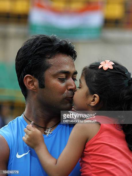 Daughter of Indian tennis player Leander Paes gives him a kiss to congratule his win in the doubles match with Mahesh Bhupathi to Brazilian pair...