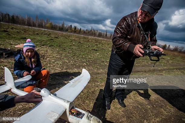 Daughter of one of the students watches her father helps a trainer to repair drone used for training Ukrainian soldiers to control unmanned aerial...