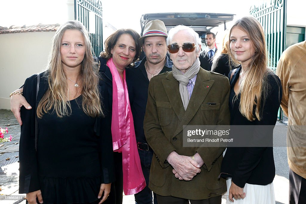 Daughter of Pierre Huth, Nathalie Huth-Guizol (2nd L) with her daughters Alice and Claire Guizol (1st L and 1st R) and Singer Charles Aznavour (2nd R) with his son Mischa Aznavour (3rd L) attend President of FIFA protocol Doctor Pierre Huth Funeral in Nogent Sur Marne cemetery on August 30, 2013 in Nogent-sur-Marne, France.