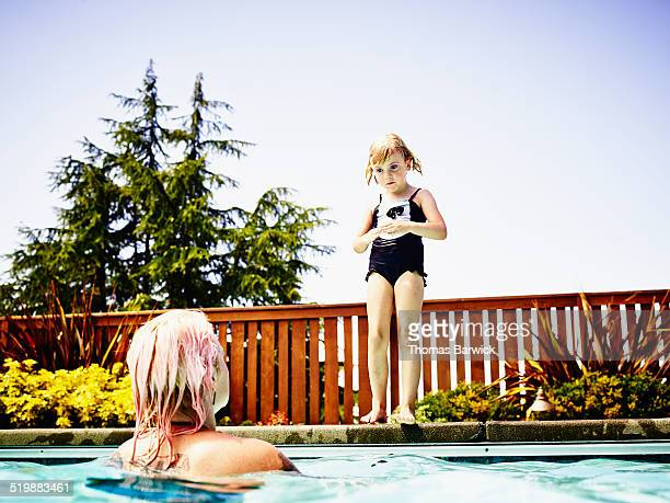 daughter on pool deck preparing to jump to mother - taking the plunge stock photos and pictures