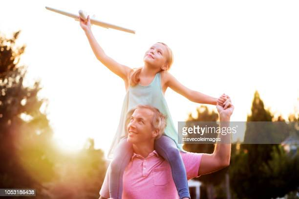 Daughter on Shoulders of Father in Park