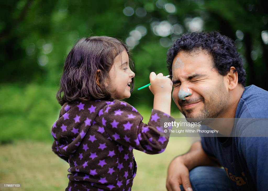 Daughter paints Daddy's face : Stock Photo