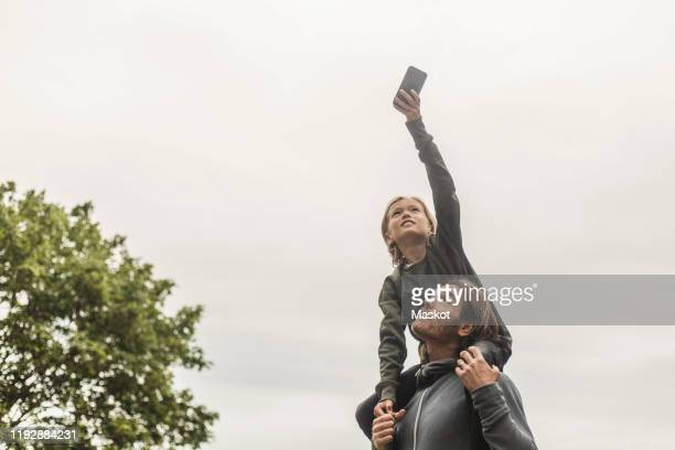 daughter photographing through smart phone while sitting on father's shoulders against clear sky - searching stock pictures, royalty-free photos & images