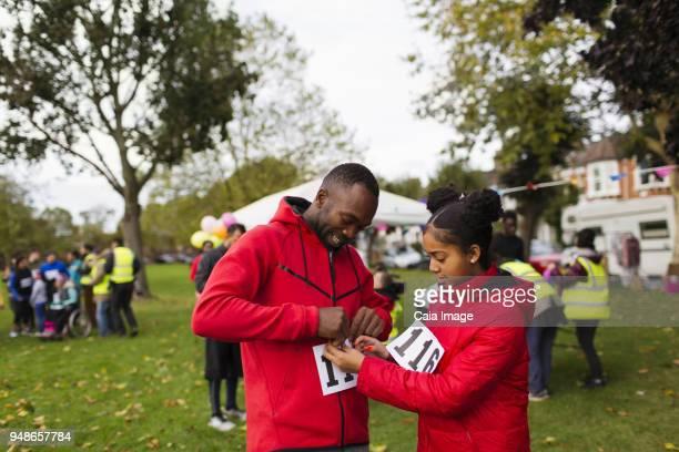 daughter pinning marathon bib on father runner at charity run in park - 40s pin up girls stockfoto's en -beelden