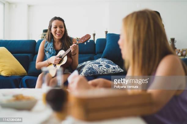 dochter spelen cavaquinho voor haar moeder - focus op achtergrond stockfoto's en -beelden