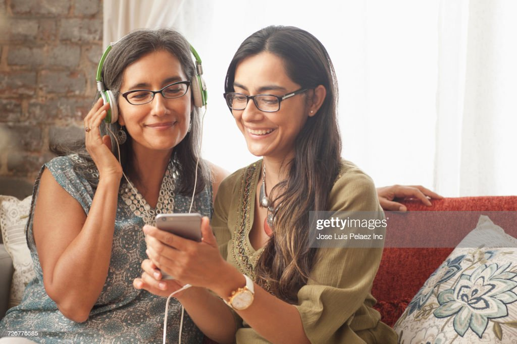 Daughter playing music on cell phone for mother : Stock Photo
