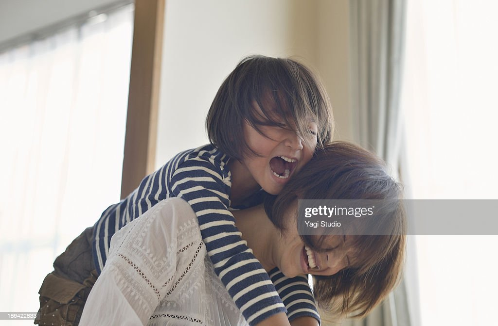 Daughter playing with Mother in the room : Stock Photo