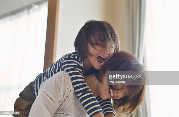 daughter playing with mother in the room - espontânea imagens e fotografias de stock