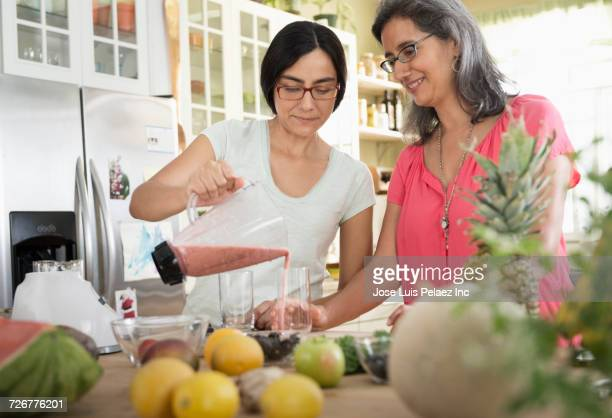 Daughter pouring smoothie from blender for mother in domestic kitchen