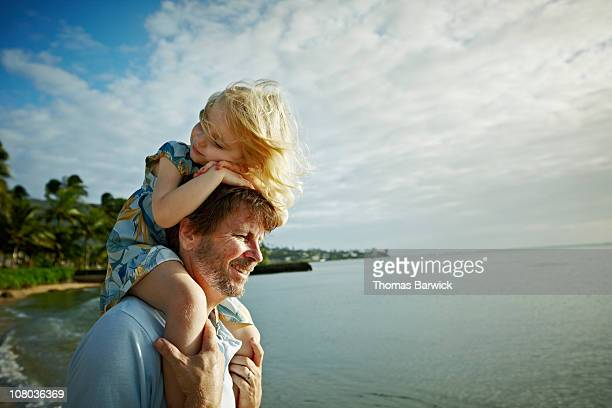 daughter riding on fathers shoulders on beach - carrying on shoulders stock pictures, royalty-free photos & images