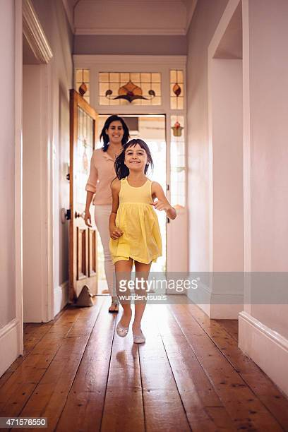 Daughter running ahead of her mom into their new home