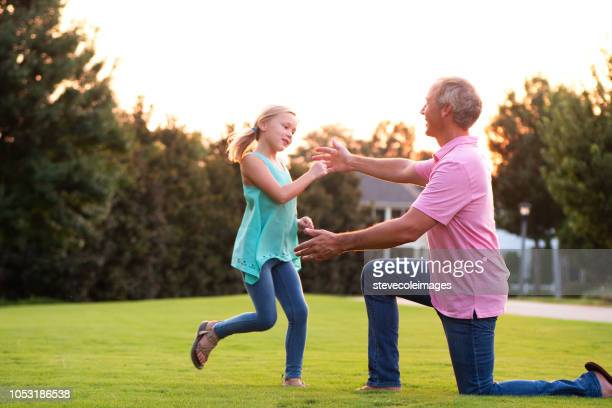 Daughter Running into Fathers Arms in Park