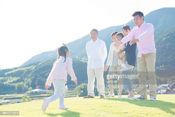 Daughter Running Towards Parents and Grandparents