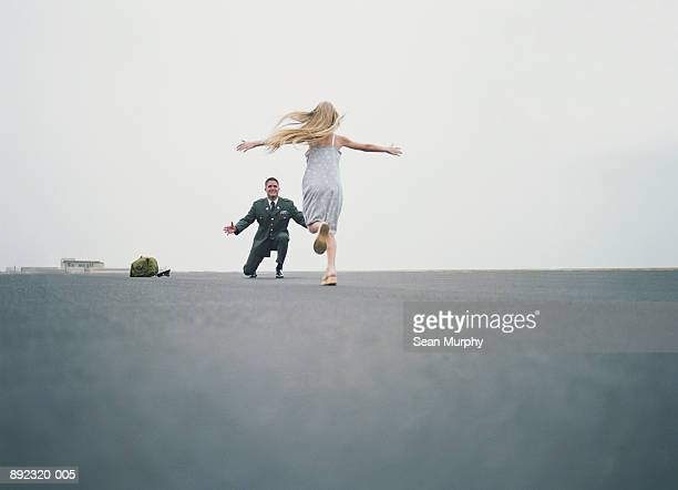 Daughter (10-12) running towards soldier at military base