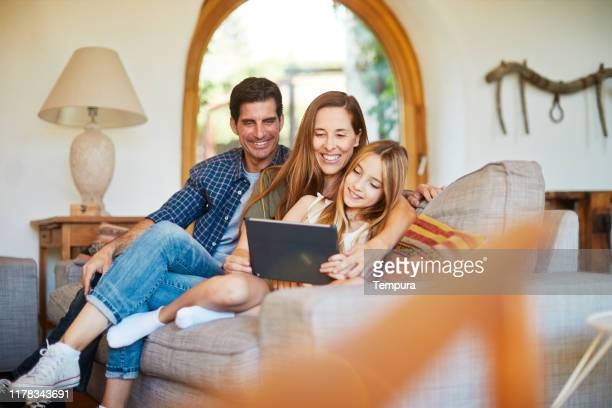 daughter sharing a digital tablet with her parents. - family at home stock pictures, royalty-free photos & images