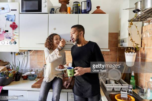 daughter sharing a piece of cake with father in kitchen at home - feeding stock pictures, royalty-free photos & images