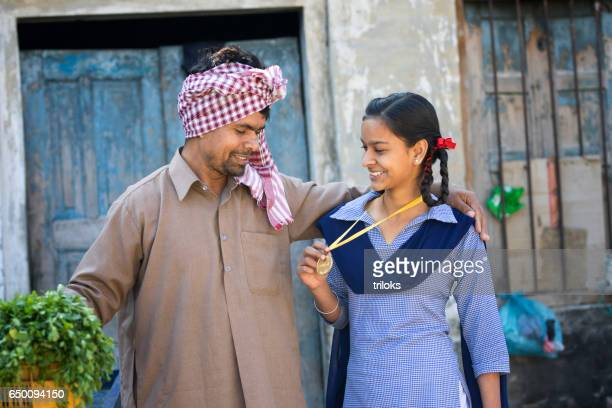 Daughter showing medal to father