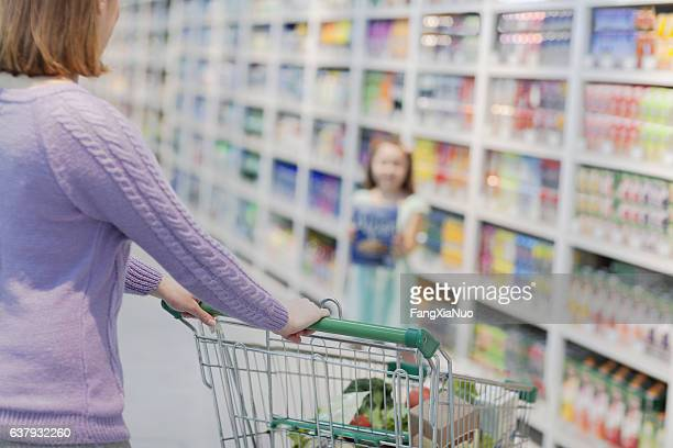 Daughter showing mother box of cereal in supermarket