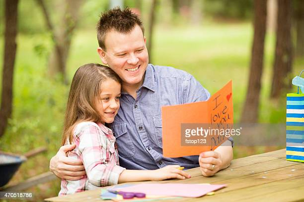 daughter shows dad handmade father's day card. outdoors. child, parent. - i love you stock pictures, royalty-free photos & images