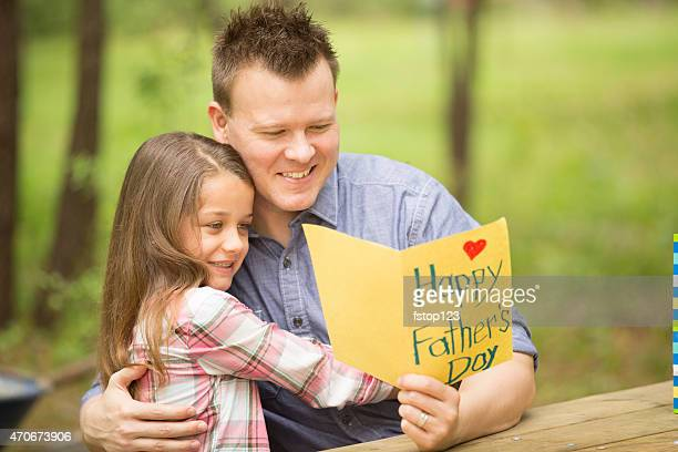 daughter shows dad handmade father's day card. outdoors. child, parent. - fathers day stock pictures, royalty-free photos & images